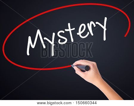 Woman Hand Writing Mystery With A Marker Over Transparent Board .