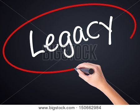 Woman Hand Writing Legacy With A Marker Over Transparent Board