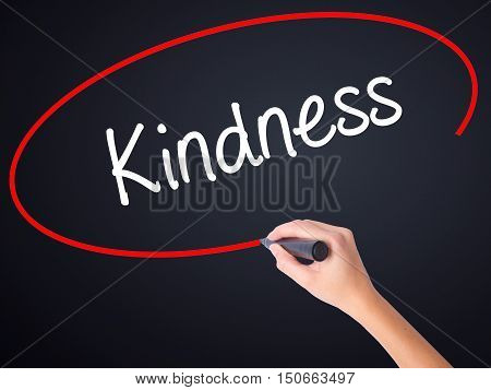 Woman Hand Writing Kindness With A Marker Over Transparent Board