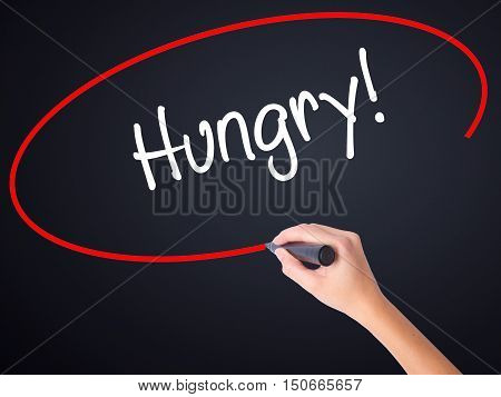 Woman Hand Writing Hungry! With A Marker Over Transparent Board