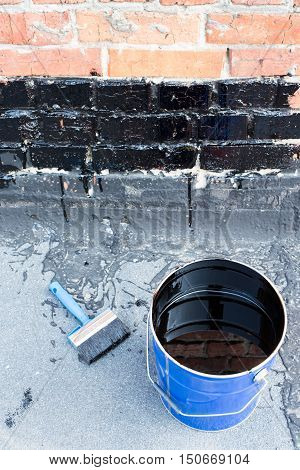 Ceiling brushes Brushes and a bucket of bitumen primer for waterproofing against the background of a brick wall. Tools for waterproofing.