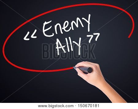Woman Hand Writing Enemy - Ally With A Marker Over Transparent Board .