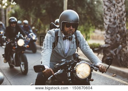 ALICANTE SPAIN - SEPTEMBER 25 2016: Male rider on motorcycle is driving his motorbike and is wearing helmet and leather gloves on the Distinguished Gentleman's Ride day a global fundraiser for prostate cancer and men's health investigation