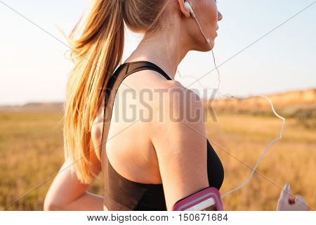 Cropped image of a blonde sports woman running with earphones outdoors
