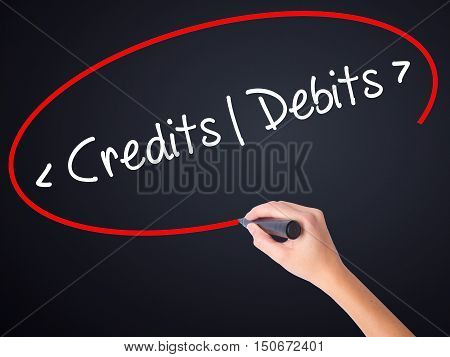 Woman Hand Writing Credits - Debits With A Marker Over Transparent Board .