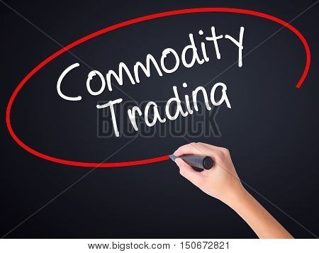 Woman Hand Writing Commodity Trading With A Marker Over Transparent Board .