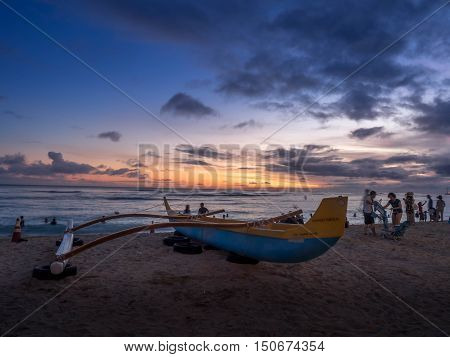 HONOLULU, USA - AUG 8: Hawaiian canoe at dusk on Waikiki beach on August 8, 2016 in Honolulu, Usa. Waikiki beach is neighborhood of Honolulu, best known for white sand and surfing.
