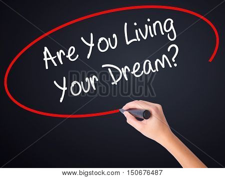 Woman Hand Writing Are You Living Your Dream? With A Marker Over Transparent Board