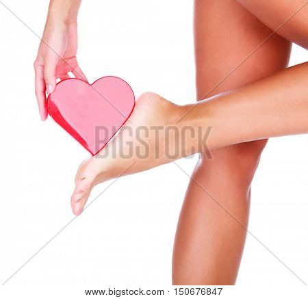 Woman's foot and red heart, isolated on white background