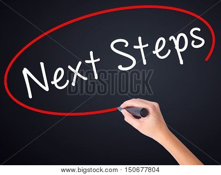Woman Hand Writing Next Steps With A Marker Over Transparent Board