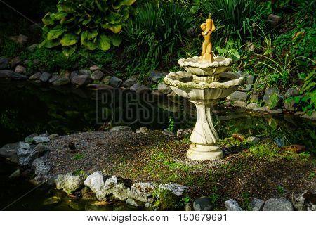 Old fountain under dappled shade in the Halifax Public Gardens, Halifax, Nova Scotia, Canada.