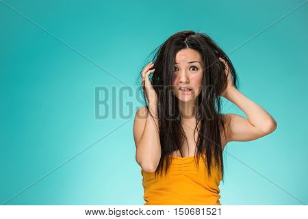 Frustrated young woman having a bad hair on blue