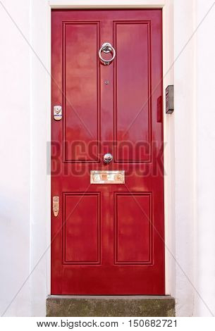 Closed red residential entrance door with knocker