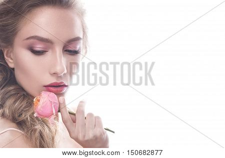 Beautiful girl in image of bride with flower. Model with nude makeup and a rose in her hand. Beauty face. Photo was taken in a studio.