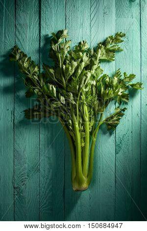 Whole Celery with Leaves on Aquamarine Wood