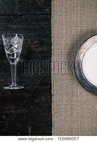 Still life with empty wineglass and plate on the half covered table. Flat lay