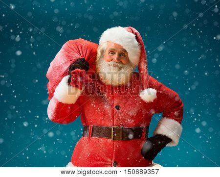 Smiling Santa Claus carrying big bag full of gifts to children on blue background. Merry Christmas & New Year's Eve concept.