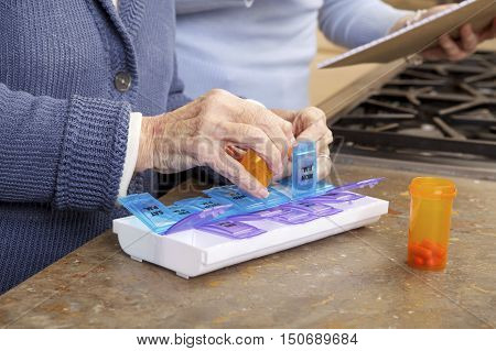 Close up of Elderly Woman Getting Help Organizing her prescription medicine into a pill box by