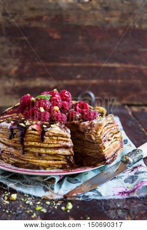 Stack of wheat golden pancakes or pancake cake with freshly picked raspberry, chopped pistachios, chocolate sauce on a dessert plate, selective focus