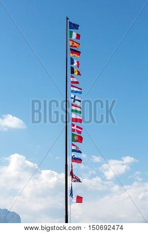 The National flags and the flag of the European Union flying in the wind in front of a blue sky.