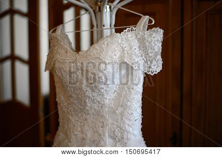 Top wedding dress lace for bride hanging on the rack. White wedding dress waiting for the bride. Clothes for the wedding ceremony.