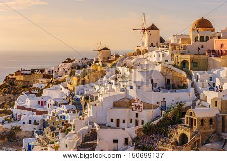 Oia, Santorini, Greece, - April 23th, 2015: Tourists enjoy famous view of Oia village with windmills at the Santorini Island in rays of sunset