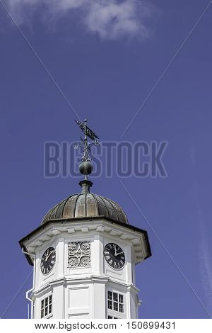Traditional round clock tower and weather vane. Shot against a blue sky with natural copy space.