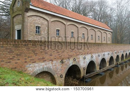 restored sluice house or Schuivenhuisje in dutch language along the hand-dug almelo nordhorn canal in the netherlands