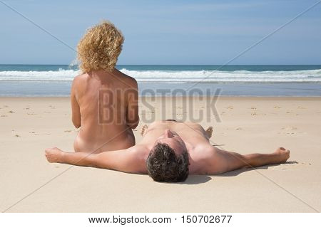 Relaxing Nudist Couple Sitting And Lying On Beach