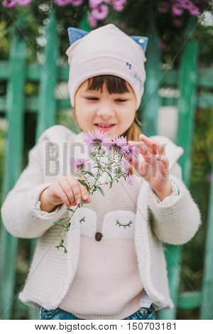 girl sniffs a flower. on a background of green fence