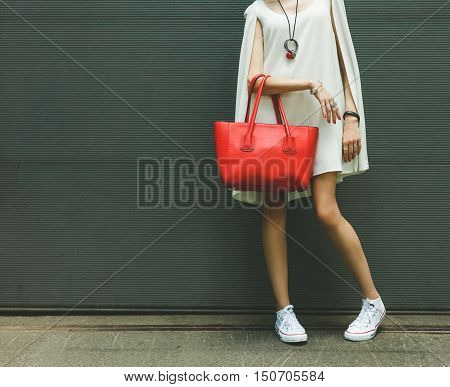 Fashionable beautiful big red handbag on the arm of the girl in a fashionable white dress and sneakers posing near the wall on a warm summer night. Warm color.