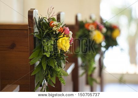 Shallow depth of field shot of flowers decorating pew for wedding
