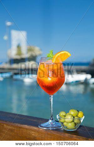 Cold glass of aperol spritz wit olive appetizer with sea and blue sky background