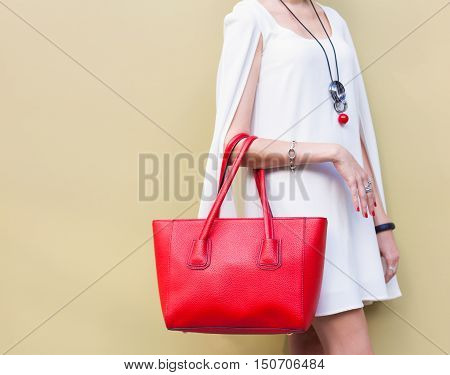 Fashionable beautiful big red handbag on the arm of the girl in a fashionable white dress posing near the wall on a warm summer night. Warm color. Close up. Part of body.