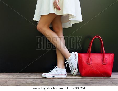 Beautiful fashionable big red handbag standing next to leggy woman in white short dress and white sneakers. Part of body.