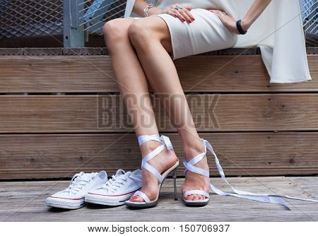 Ribbon Tie Stilleto shoe and sneakers. Fashionable woman with long beautiful legs sitting on a wooden board and disguises footwear Part of body.