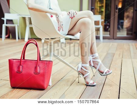 Girl sitting of summer cafe with a big red super fashionable handbags in short white dress and high heels on a warm summer evening. Warm colors