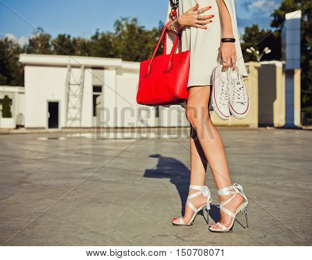 Fashion and style. Leggy girl stands in a park on a summer evening in a short white dress and holding a sneakers and big red fashionable handbag