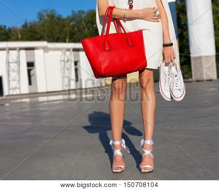 Fashion and style. Leggy girl stands in a park on a summer evening in a short white dress and holding a sneakers and big red fashionable handbag. Part of body.