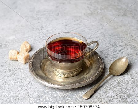 Vintage tea in a mug on a metal saucer on a gray background