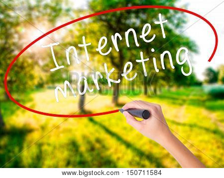 Woman Hand Writing Internet Marketing With A Marker Over Transparent Board