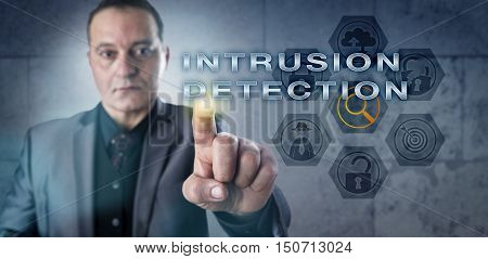 Determined but concerned looking mature system administrator is activating INTRUSION DETECTION onscreen. Computer and network security concept for monitoring a system for malicious activity.