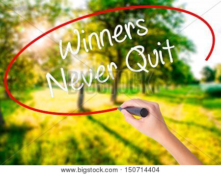 Woman Hand Writing Winners Never Quit With A Marker Over Transparent Board