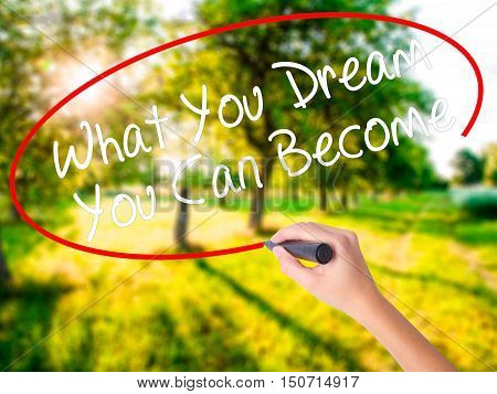 Woman Hand Writing What You Dream You Can Become With A Marker Over Transparent Board