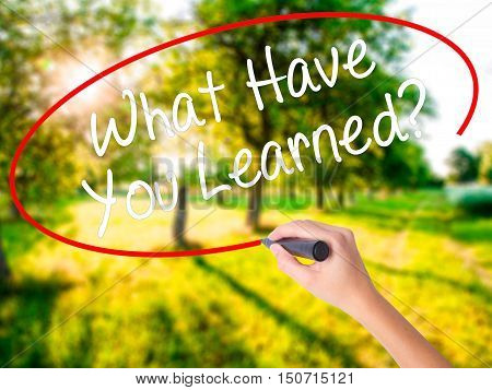 Woman Hand Writing What Have You Learned? With A Marker Over Transparent Board