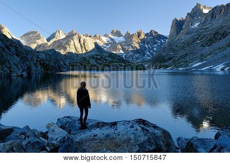 Woman Hiker Looking Towards Lake and Alpine Skyline.  Titcomb Basin, The Wind River Range, Wyoming