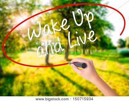 Woman Hand Writing Wake Up And Live With A Marker Over Transparent Board .