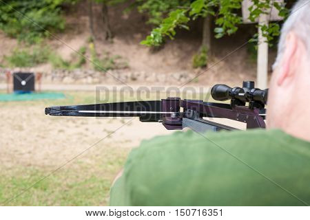 The Targeting with a black scoped crossbow