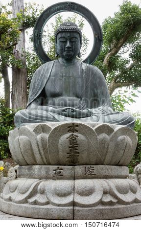 Kyoto Japan - September 15 2016: At the Shinnyo-do Buddhist Temple the stone statue of the meditating or Amithabha Buddha stands in the garden. He sits on lotus and has big halo.
