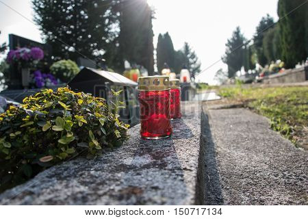 Votive candles lantern on the grave in Slovak cemetery. All Saints' Day. Solemnity of All Saints. All Hallows eve. 1st November. Feast of All Saints. Hallowmas. All Souls' Day